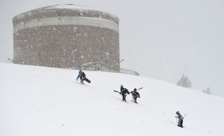 Sledder's and skier's climb the hill at Woodland Reservoir Monday, Nov.21, 2016, with Syracuse's first snowstorm of the season that belted the area. At least ten inches covered the area along with high winds. (Dennis Nett/The Syracuse Newspapers via AP)