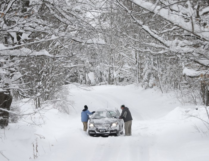 Motorists clear lake-effect snow from a vehicle on a road, Monday, Nov. 21, 2016, in Grafton, N.Y. (AP Photo/Mike Groll)