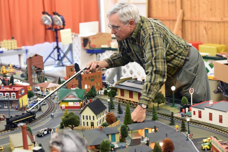 John Palese, a volunteer at The Fire Museum of Maryland, picks up a Lionel steam locomotive as he readies the museum's annual train garden for the season opening on November 26.  (Kim Hairston/Baltimore Sun)