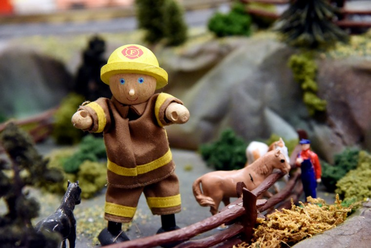 A giant wooden firefighter watches visitor to The Fire Museum of Maryland's annual train garden from inside a horse corral. The train garden opens on November 26.  (Kim Hairston/Baltimore Sun)