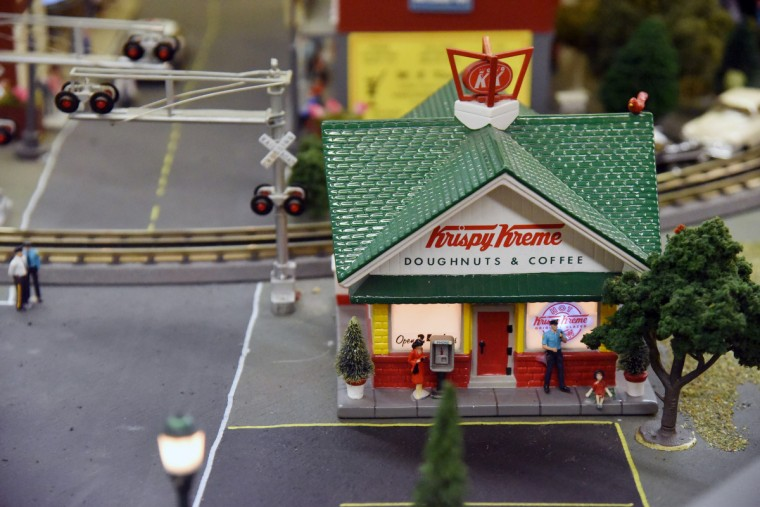 A Krispy Kreme doughnut shop with a pay phone and a police officer are part of The Fire Museum of Maryland's annual train garden that opens on November 26.  (Kim Hairston/Baltimore Sun)