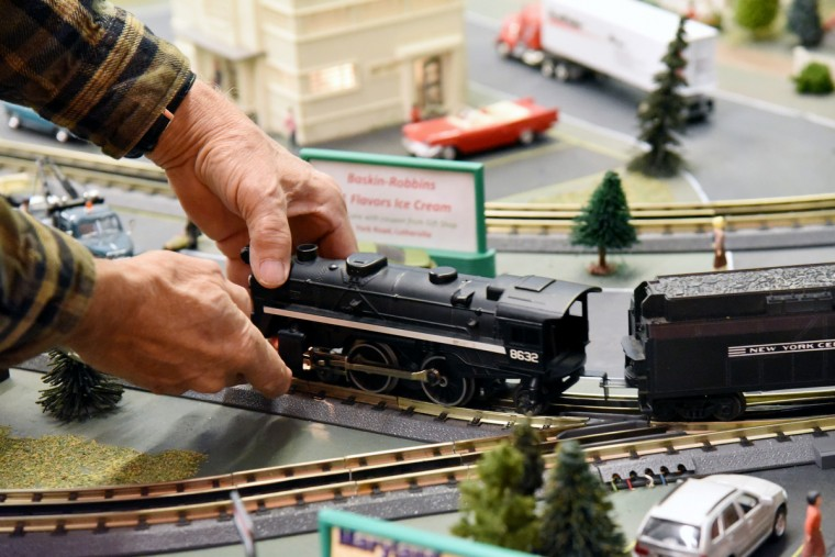 John Palese, a volunteer at The Fire Museum of Maryland, works on the museum's annual train garden.  Many local businesses and landmarks are represented in the model railroad display that opens on November 26.  (Kim Hairston/Baltimore Sun)