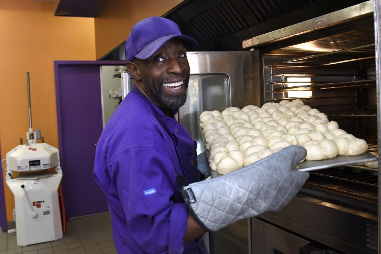 "James Hamlin, owner of The Avenue Bakery, pulls a tray of his famous ""Poppay's"" dinner rolls from the dough proofer. Next, they'll be transferred to the oven for baking. Thanksgiving means making hundreds of dozens of ""Poppay's"" yeast dinner rolls at The Avenue Bakery on Pennsylvania Avenue in the Druid Heights neighborhood. (Barbara Haddock Taylor/Baltimore Sun)"