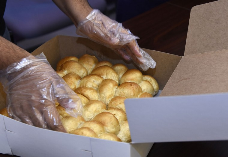 """Rolls being boxed at The Avenue Bakery. Thanksgiving means making hundreds of dozens of """"Poppay's"""" yeast dinner rolls at The Avenue Bakery on Pennsylvania Avenue in the Druid Heights neighborhood. (Barbara Haddock Taylor/Baltimore Sun)"""