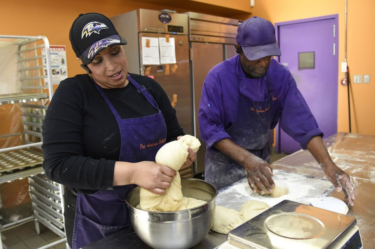 Belinda Frederick, left, helps her father James Hamlin, right, knead dough for his famous dinner rolls. (Barbara Haddock Taylor/Baltimore Sun)