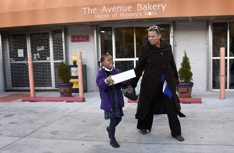 "Regular customers Grace, 8, left, and Jules Howie, right, are happy as they leave The Avenue Bakery with a dozen rolls.  Thanksgiving means making hundreds of dozens of ""Poppay's"" yeast dinner rolls at The Avenue Bakery on Pennsylvania Avenue in the Druid Heights neighborhood. Ms. Howie said the bakery is ""a beacon of light in the community.""   (Barbara Haddock Taylor/Baltimore Sun)"