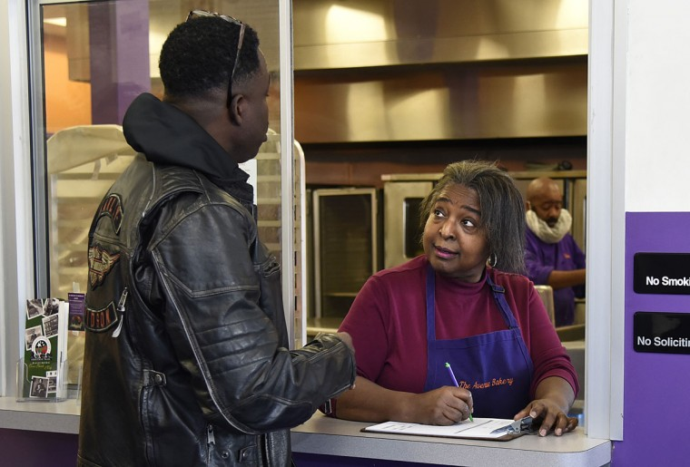 Roosevelt Hammett, left, of Baltimore, gives his order to Susan Dezurn, right, who is working behind the window at The Avenue Bakery.  (Barbara Haddock Taylor/Baltimore Sun)
