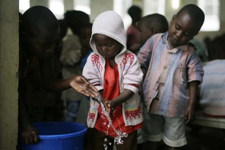In this photo taken on Saturday, June 18, 2016, orphans wash their hands before eating their lunch at the Don Bosco center in Goma, Democratic Republic of Congo. More than four million children have lost at least one parent in Congo over the past two decades. (AP Photo/Jerome Delay)