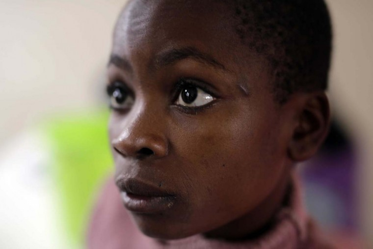 In this photo taken on Saturday, June 18, 2016, Julie Faide, 14, waits for lunch to be served at the Don Bosco center in Goma, Democratic Republic of Congo. Julie came to the center in 2003. Her father was a soldier and her mother has disappeared. Julie wants to be a nun. (AP Photo/Jerome Delay)