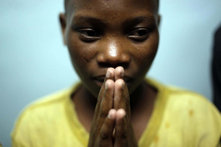 "In this photo taken on Saturday, June 18, 2016, Jean Claude Twisenge, 15, from Massissi, joins other street children in a prayer service at a Don Bosco safe house in Goma, Democratic Republic of Congo. Jean Claude had walked for a week to reach Goma, ""Fleeing misery, I was looking for money to pay for school"". (AP Photo/Jerome Delay)"