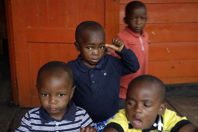 In this photo taken on Sunday, June 19, 2016, five-year-old Alpha Meleki, center, plays in the yard at the En Avant Les Enfants INUKA center in Goma, Democratic Republic of Congo. Melee survived an attack from ADF rebels on his village that left over 20 dead including his parents in Beni in January 2016. Rescuers found Meleki in a pile of bodies with a bullet wound to his belly. (AP Photo/Jerome Delay)