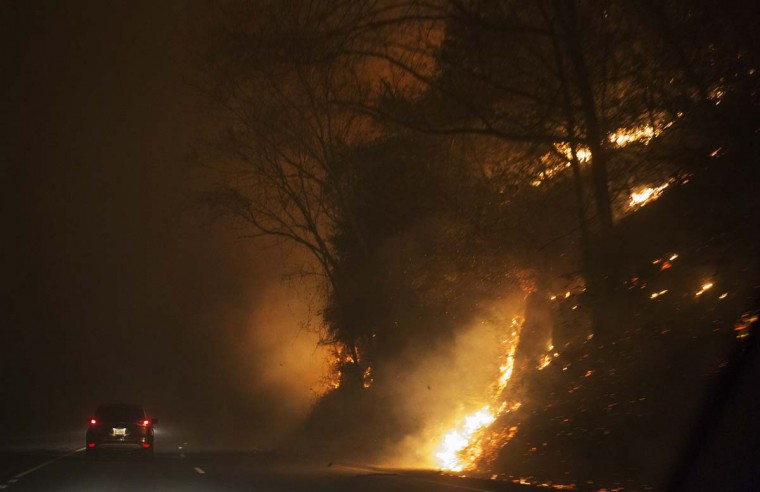 Fire erupts on the side of The Spur on Highway 441 between Gatlinburg and Pigeon Forge, Tenn., Monday, Nov. 28, 2016. In Gatlinburg, smoke and fire caused the mandatory evacuation of downtown and surrounding areas, according to the Tennessee Emergency Management Agency. (Jessica Tezak/Knoxville News Sentinel via AP)