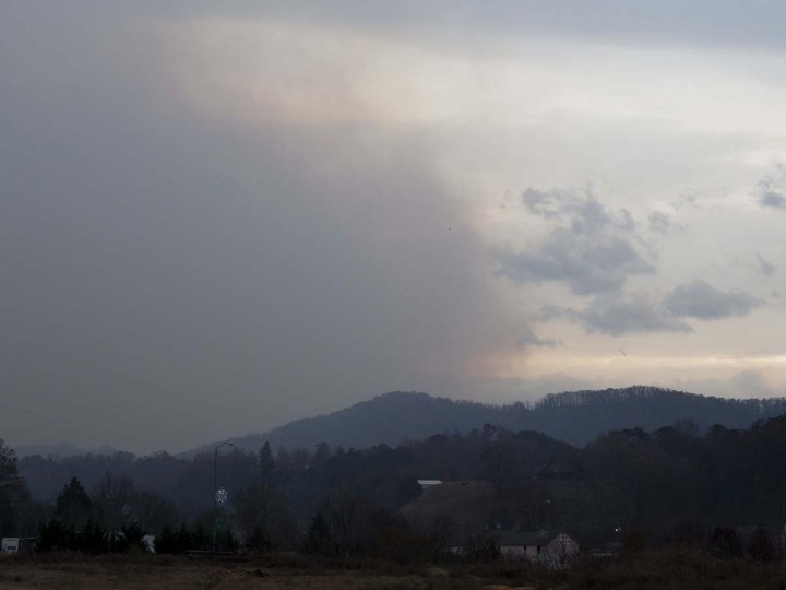 Smoke rises from the Great Smoky Mountains as seen from Pigeon Forge, Monday, Nov. 28, 2016. Gatlinburg officials say several areas are being evacuated as a result of fires in and around Great Smoky Mountains National Park. (Brianna Paciorka/Knoxville News Sentinel via AP)