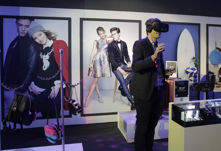 "A man wearing a viewer headset experiences augmented reality intelligent for shopping at an exhibition during the ""Singles' Day"" global online shopping festival in Shenzhen, southern China's Guangdong province Friday, Nov. 11, 2016. In a bright spot for China's cooling economy, online shoppers spent billions of dollars Friday on ""Singles Day,"" a quirky holiday that has grown into the world's busiest day for e-commerce. (AP Photo/Kin Cheung)"