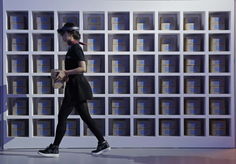 "An attendant wearing a viewer headset, matches the boxes as she demonstrates the augmented reality intelligent at an exhibition during the ""Singles' Day"" global online shopping festival in Shenzhen, southern China's Guangdong province Friday, Nov. 11, 2016. In a bright spot for China's cooling economy, online shoppers spent billions of dollars Friday on ""Singles Day,"" a quirky holiday that has grown into the world's busiest day for e-commerce. (AP Photo/Kin Cheung)"