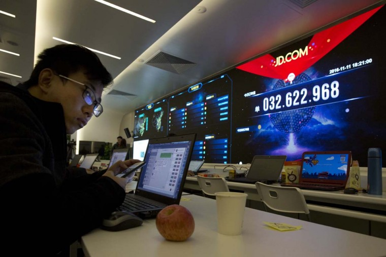 "A Chinese worker looks up near screens displaying the movement of packages around China at the JD.com command center in Beijing, China, Friday, Nov. 11, 2016. In a bright spot for China's cooling economy, online shoppers spent billions of dollars Friday on ""Singles Day,"" a quirky holiday that has grown into the world's busiest day for e-commerce. (AP Photo/Ng Han Guan)"