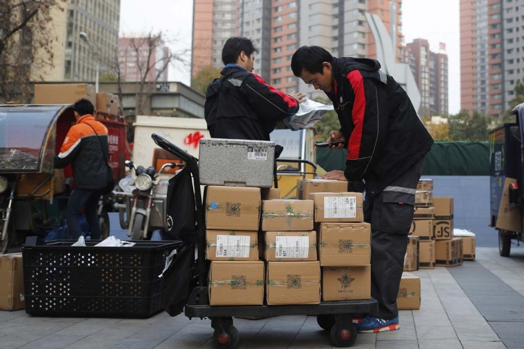 "Delivery workers sort parcels for their customers in Beijing, Friday, Nov. 11, 2016. In a bright spot for China's cooling economy, online shoppers spent billions of dollars Friday on ""Singles Day,"" a quirky holiday that has grown into the world's busiest day for e-commerce. (AP Photo/Andy Wong)"