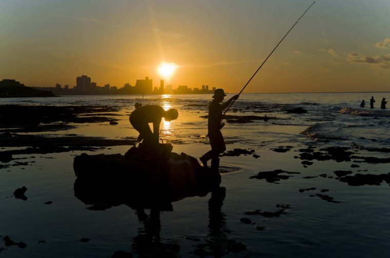 In this Nov. 11, 2016 photo, fishermen throw their fishing rods from Chivo beach as the sun sets in Havana, Cuba. Cuba has been renowned for its fishing at least since the days of Ernest Hemingway, and foreigners by the thousands come each year to fish in waters largely protected by Cuba's lack of development. (AP Photo/Ramon Espinosa)