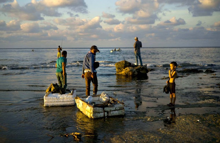 "In this Nov. 11, 2016 photo, young fishermen pull their rafts made out of foam as they head to sea from Chivo Beach in Havana, Cuba. Many Cubans have taken to riding out on blocks of industrial foam to catch larger fish, but the unsafe technique known as ""cork fishing,"" has become the target of frequent coast guard crackdowns with steep fines. (AP Photo/Ramon Espinosa)"