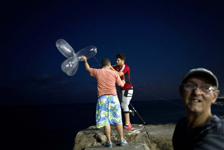 "This Nov. 12, 2016 photo shows Derek Aguiar Gonzalez, a stomatology student and amateur fisherman who said he takes home what he catches, preparing to cast his line, fitted with inflated condoms that serve to keep the bait high in the water and increase the line's resistance against the pull of heavy fish, at the malecon seawall in Havana, Cuba. Few are as creative as what Havana's fishermen call ""balloon fishing,"" a technique employing a couple of cents worth of condoms to pull fish worth an average month's salary from the ocean. (AP Photo/Ramon Espinosa)"