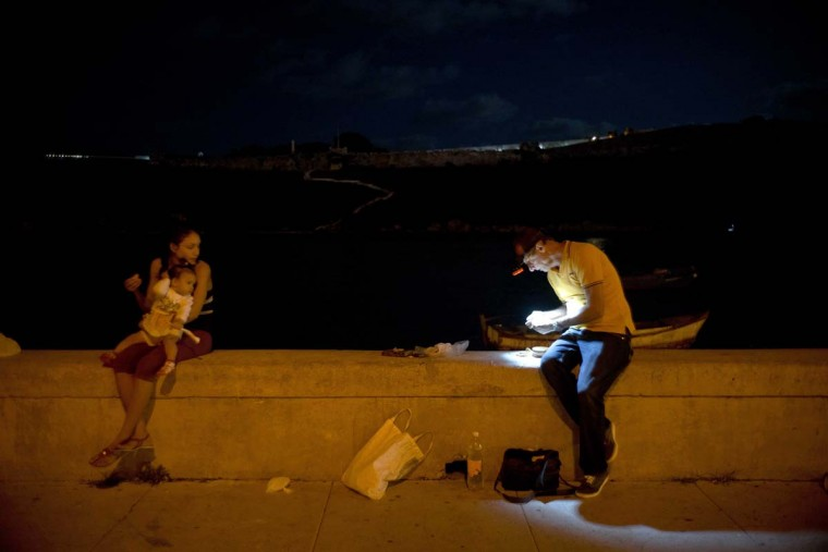 In this Nov. 13, 2016 photo, a man prepares his fishing gear on the malecon seawall in Havana, Cuba. Much of Cuba's coastline remains free of the large-scale building that has damaged ecosystems in the rest of the Caribbean. (AP Photo/Ramon Espinosa)