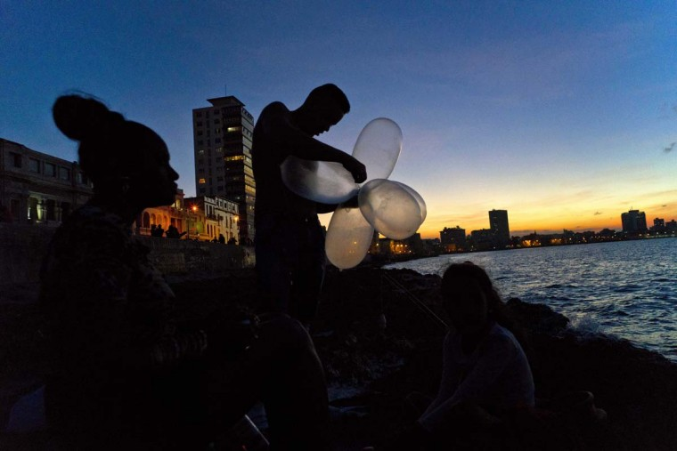 "In this Nov. 13, 2016 photo, mechanic Junior Torres Lopez ties inflated condoms together for his fishing line to keep his bait high in the water and increase his line's resistance against the pull of heavy fish, as his wife Edelmis Ferro Solano sits nearby along the malecon sea wall, at sunset in Havana, Cuba. Dozens of men can be found ""balloon fishing"" along the Havana seawall at night, using their homemade floats to carry their lines as far as 900 feet into the coastal waters. (AP Photo/Ramon Espinosa)"
