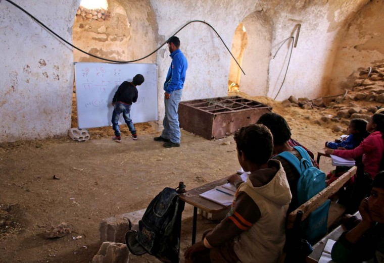 A Syrian boy practices basic arithmetic operations with a teacher during class in a barn that has been converted into a makeshift school to teach internally displaced children from areas under government control, in a rebel-held area of Daraa, in southern Syria on November 10, 2016. Rebels hold most of Daraa province, but the regional capital is largely controlled by the government. (MOHAMAD ABAZEED/AFP/Getty Images)