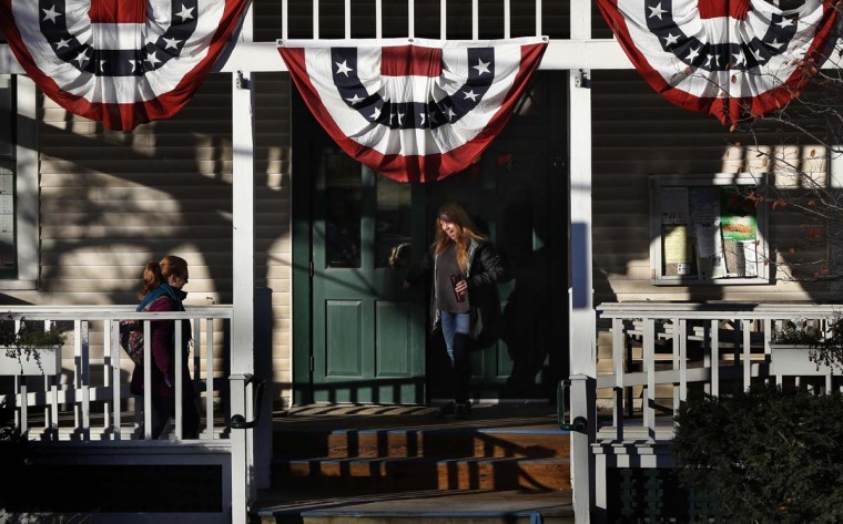 """Amanda Pacilli, 29, holds the door open for a fellow voter arriving at the town hall, Tuesday, Nov. 8, 2016, in Hinesburg, Vt. """"I'm so relieved that Election Day is finally here,"""" said Pacilli. """"I'm just happy to see other people involved in voting."""" (AP Photo/Robert F. Bukaty)"""