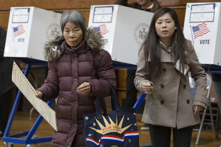 A voter, left, carries her ballot, while being assisted by interpreter Ping Chan, Tuesday, Nov. 8, 2016, in the Sunset Park neighborhood in the Brooklyn borough of New York. The voter, originally from China, declined to give her name. (AP Photo/Mark Lennihan)