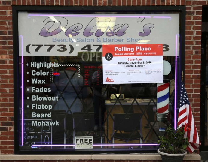 A Polling Place poster is taped to the window of Delia's Beauty Salon on 55th Street on Tuesday, Nov. 8, 2016, in Chicago. (AP Photo/Charles Rex Arbogast)