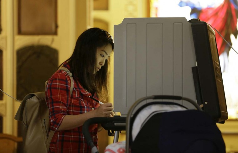 Serene Wetzell, a Chinese-American, votes at the Neptune Society Columbarium Tuesday, Nov. 8, 2016, in San Francisco. Built in 1898, the columbarium is one of the last remaining cemeteries in San Francisco. (AP Photo/Eric Risberg)