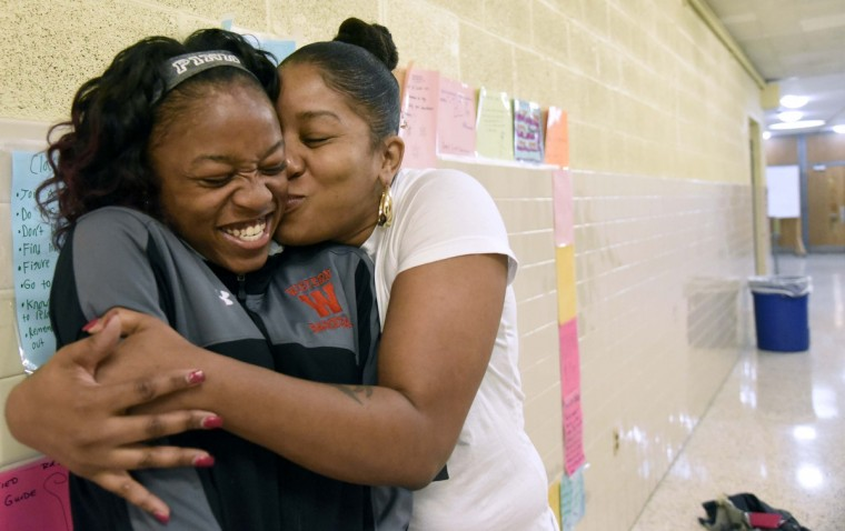 "Kyaja ""JJ"" Williams, 17, gets a hug and kiss from her mother, Vanessa Williams,  outside the Western High School auditorium.  The school is celebrating their graduating seniors on their college signing day. This is part of a national effort to give college bound students the type of recognition athletes receive. (Kim Hairston/Baltimore Sun)"