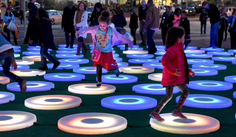 "Children play on ""The Pool"" by Jen Lewin, a series of color-changing circles that react to movement of festival-goers. (Jerry Jackson/Baltimore Sun)"