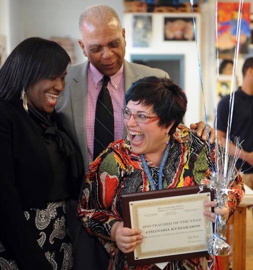 Athanasia Kyriakakos, an art teacher at Mergenthaler Vocational-Technical High School, was named Baltimore city teacher of the year and was presented with flowers, balloons and a certificate by City Schools CEO Gregory Thornton (standing in background). On left is Ketia Stokes, who was the 2013 teacher of the year.  (Barbara Haddock Taylor/Baltimore Sun)