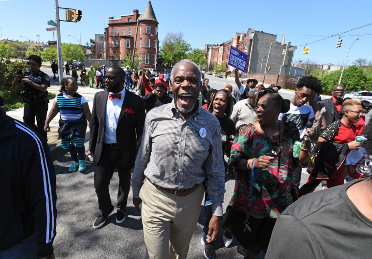 "Actor Danny Glover, center, yells out protest slogans as he marched with hundreds in Rev. Jamal Bryant's ""Unity March"" from Penn/North to The Freddie Gray Empowerment Center on Eutaw Place to mark the anniversary of Gray's death in police custody and to calls for change in Baltimore. (Kenneth K. Lam/Baltimore Sun)"
