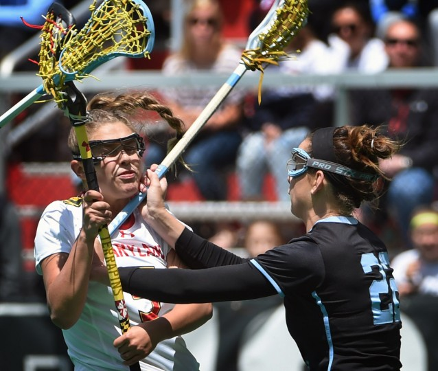 Maryland's Jen Giles, left, is cross checked by Johns Hopkins' Shannon Fitzgerald in the first half. Maryland defeated Johns Hopkins by score of 14 to 8 in the 2016 NCAA women's lacrosse tournament. (Kenneth K. Lam/Baltimore Sun)
