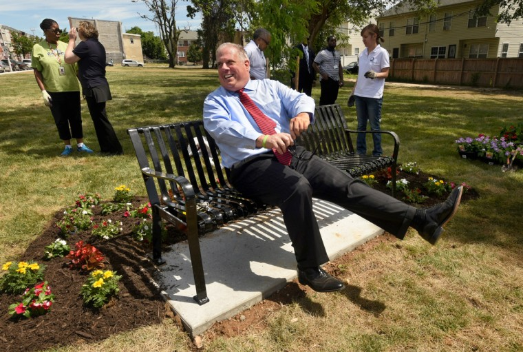 Gov. Larry Hogan tries out one of two benches in a new green space in the 1000 block of North Stricker Street in Sandtown, where a block of vacant rowhouses was torn down recently. A group of small trees, sod, and some annuals were planted. (Amy Davis/Baltimore Sun)