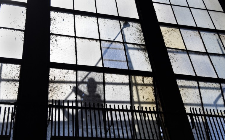 A worker cleans one of over 3000 windows on the tailrace side of turbine hall at the Exelon Conowingo Hydroelectric Plant, which has been producing electricity on the Susquehanna River since 1928. (Barbara Haddock Taylor/Baltimore Sun)