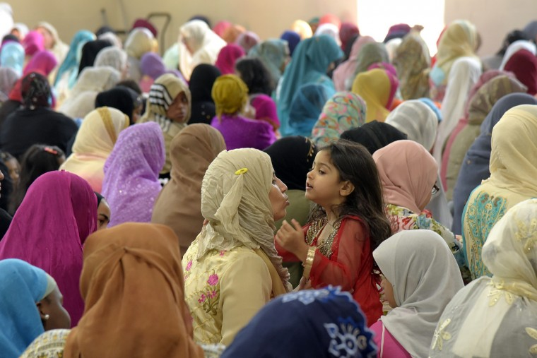 At the Islamic Society of Baltimore,  Salma Siraj tends to her daughter, Sarah Siraj, in center, during prayers marking the last day of Ramadan, a month of fasting and prayer for Muslims. (Algerina Perna/Baltimore Sun)