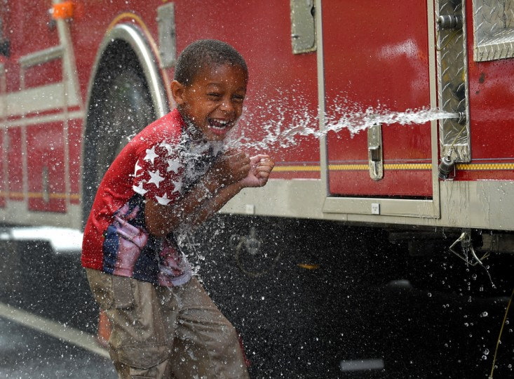 Darrin MIller, 5, of Baltimore, cools off with the help water pumped from a city fire engine used to keep people cool at Artscape.  The first full day of Artscape begins as hundreds of vendors line the streets of Baltimore to sell their work.  (Lloyd Fox/Baltimore Sun)