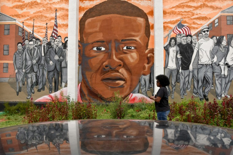 Cynthia McCollum, who works in the Sandtown neighborhood, walks past a mural honoring Freddie Gray, across the street from where Baltimore State's Attorney Marilyn Mosby held a press conference at Mount and Presbury Streets. The remaining charges against the three officers to be tried in Freddie Gray's death were dropped today. (Amy Davis/Baltimore Sun)