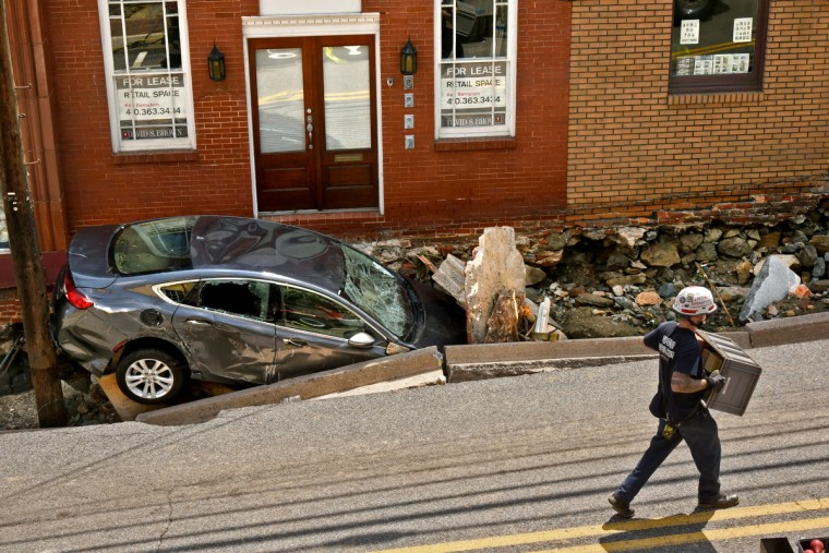 A worker carries lumber to shore up one of the stores on Main Street, near where this car fell into the hole left when the sidewalks caved in. Recovery and cleanup is underway in Ellicott City, where a state of emergency was declared after a  flash flood caused two fatalities and destroyed businesses and homes along Main Street.  (Amy Davis/Baltimore Sun)