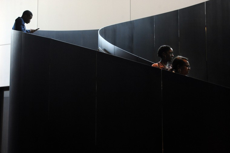 The Monumental Staircase, a curved stairway in the Smithsonian National Museum of African American History and Culture (NMAAHC), leads down to Concourse 0, the first of four levels below ground. As people moved up and down the stairs they may temporarily disappear from sight.  (Kim Hairston/Baltimore Sun)