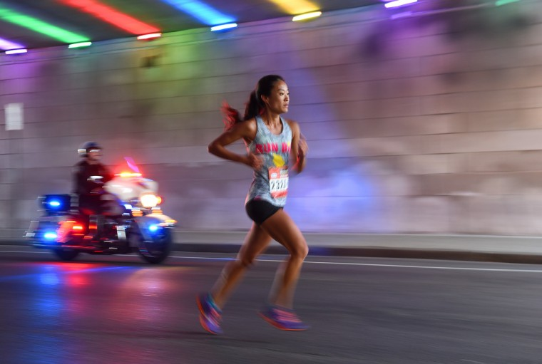 Eventual women's winner Caitlyn Tateishi nears mile nine of the 2016 Baltimore Marathon on St. Paul Street beneath the Orleans Street viaduct. (Jerry Jackson/Baltimore Sun)