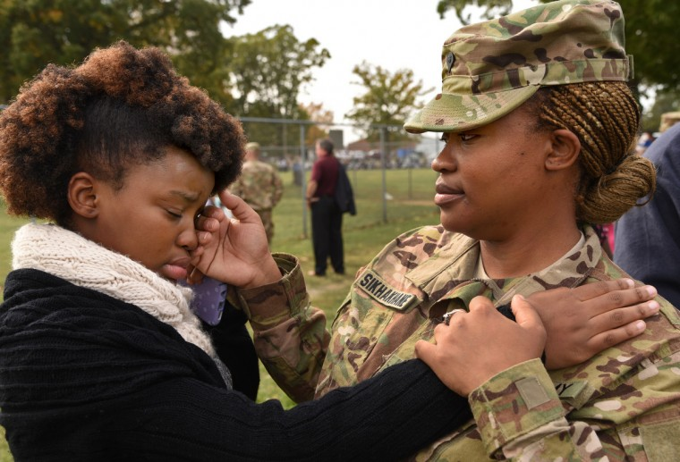 SPC Fortunate Sikhakhane, right, brushes away the tears of her daughter Luyanda Dlamini, 12, shortly before parting with the family members who came to see her off. 450 members of the Maryland and Virginia National Guard were given a departure ceremony at Fort Belvoir on Sunday before shipping out. 175 Marylanders are among those who will be serving in the Mideast with the 29th Infantry Division.   (Amy Davis/Baltimore Sun)