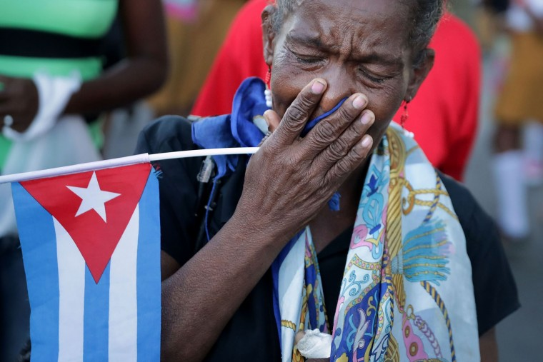 A woman weeps after watching a military convoy transport the remains of former Cuban President Fidel Castro from Revolution Plaza to the Cementerio Santa Ifigenia where he will be buried December 4, 2016 in Santiago de Cuba, Cuba. Sunday marked the last of a nine-day mourning period after Castro died November 25 at the age of 90. (Photo by Chip Somodevilla/Getty Images)