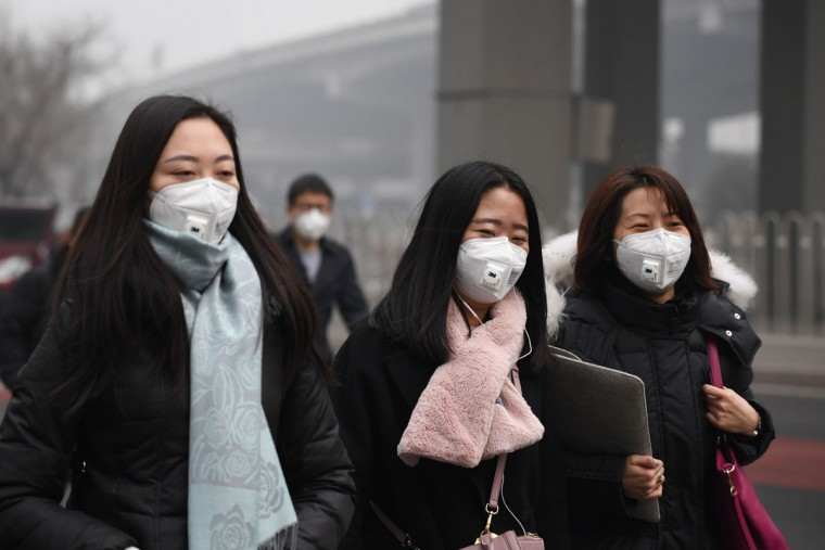 Pedestrians wear masks on a polluted day in Beijing on December 20, 2016. Heavy smog suffocated northeast China for a fifth day on December 20, with hundreds of flights cancelled and road and rail transport grinding to a halt under the low visibility conditions. (AFP PHOTO/ Greg Baker)