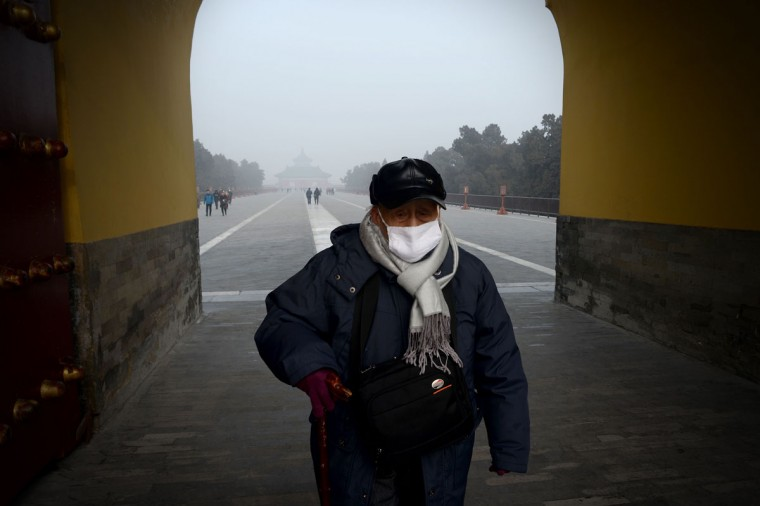 An elderly men wearing a mask walks through an arch at a the Temple of Heaven park in Beijing on December 20, 2016. Heavy smog suffocated northeast China for a fifth day on December 20, with hundreds of flights cancelled and road and rail transport grinding to a halt under the low visibility conditions. (AFP PHOTO / WANG ZHAO)