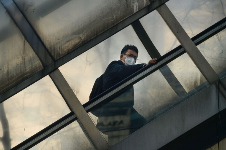 A man wearing a mask rides an escalator to cross an overpass in Beijing on December 19, 2016. Hospital visits spiked, roads were closed and flights cancelled on December 19 as China choked under a vast cloud of toxic smog, with forecasters warning the worse was yet to come. (AFP PHOTO / WANG ZHAO)