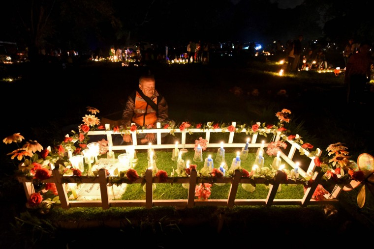 "Locals light candles at the ""Jardines de la Aurora"" cemetery in Cali, department of Valle del Cauca, Colombia, on December 7, 2016, during the celebration of the Day of the Candles -one of the most important religious holidays in Colombia which marks the beginning of the Christmas holidays. (AFP PHOTO / LUIS ROBAYOLUIS ROBAYO/AFP/Getty Images)"